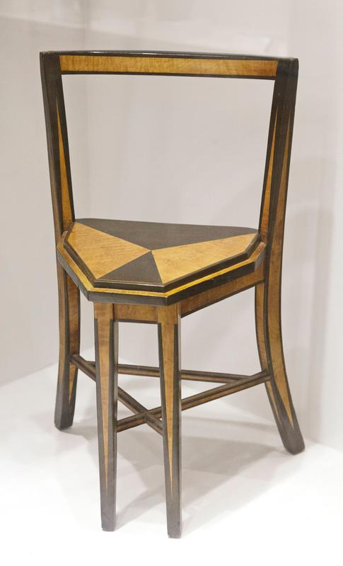 Six-sided seat; open seat back, curved at top; chair rungs form triangle; front legs close together; black triangles throughout