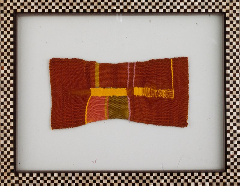 orange ground tapestry mounted between two pieces of glass and framed