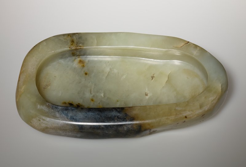 Plain Serpentine Quartz Shallow Bowl of oval shape, with thick sides and base, the translucent brownish-green stone with darker markings, the base engraved with a four-character Qianlong mark
