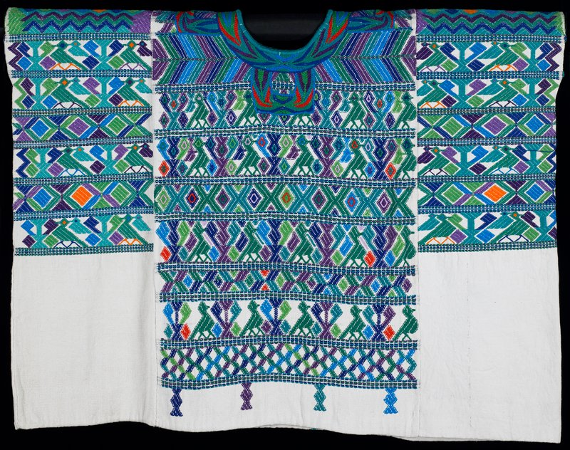 """Three panel huipil; supplementary weft patterning covers 3/4 of the garment; elaborate embroidery encircles the neck opening and four """"U"""" shapes extend from neck opening; white ground cloth with patterning primarily in green with accents in purple, blue, orange and red; design consists of rows of stylized bird and tree pattern alternating with rows of diamonds; four small 'twisted thread' motifs extend from lowest row of pattern (a signature of this town's style)."""