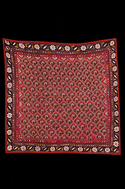 """""""Mochi work""""; red center square, bordered with black, bound in red; embroidery in overall floral pattern with blue, yellow, red, white, green; surrounded by floral border"""
