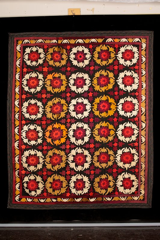 stylized flower motifs embroidered across surface; stylized foliage border; rose, red, orange, orchre, white, brown, magenta on black ground