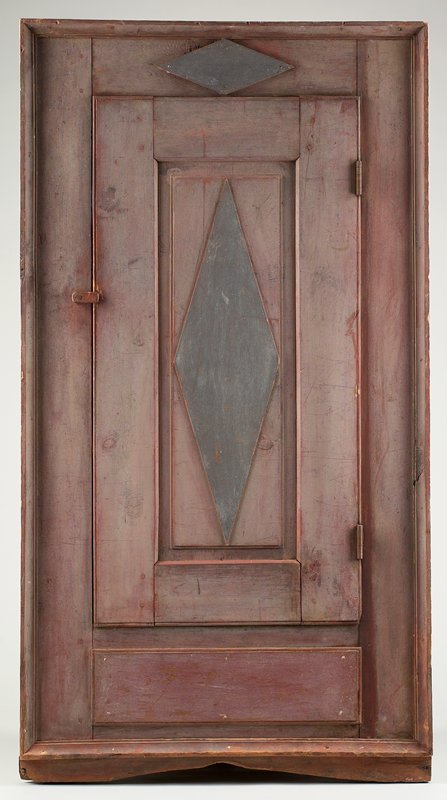 triangular-shaped corner cabinet with faded red front panel; grey-blue diamond on door and diamond above door