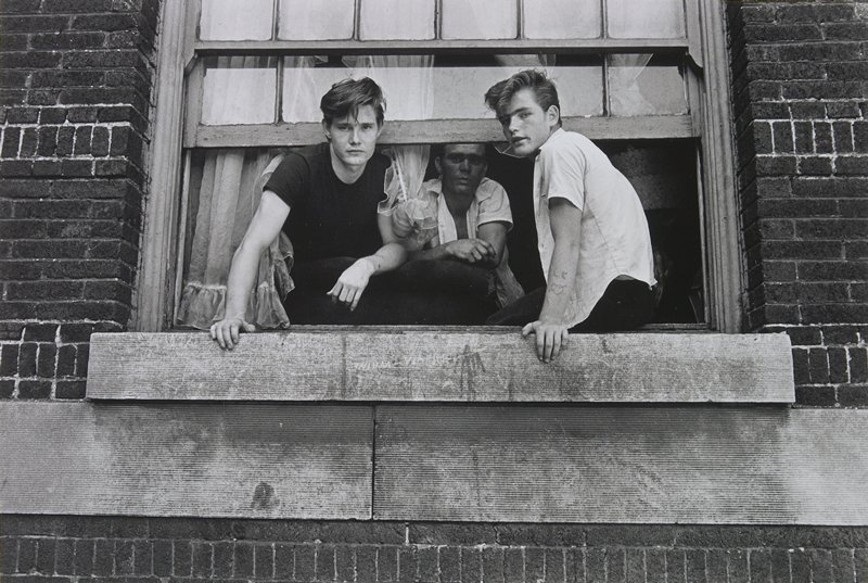 three young men at an open window; two leaning out, center figure in background