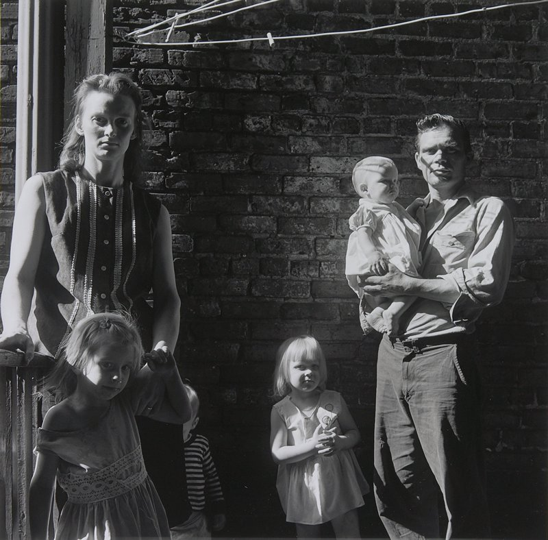 young couple with four children: man at right holding a baby; little girl on man's PR side; woman at left holding a girl's PL arm; another child hidden behind woman's skirt