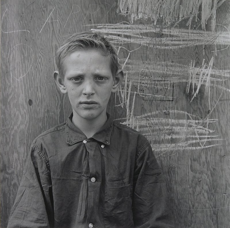 head and torso of a blonde boy with a wrinkled brow; plywood with chalk scribbles and scratches behind him