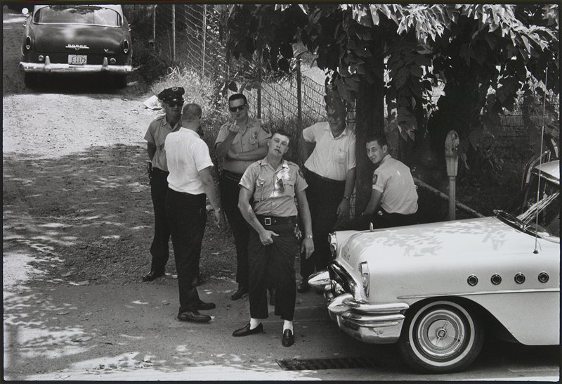 six men in a circle, with car at right; man in uniform in front, smoking a cigar, grabs his crotch; uniformed man in sunglasses behind first man extends the middle finger of his PR hand