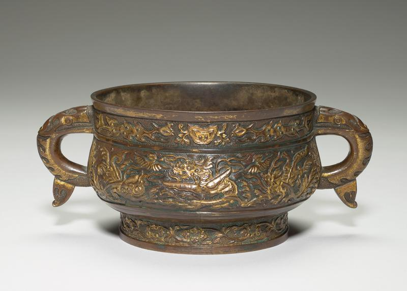 low, wide foot with flaring body and slightly inverted wide mouth; pair of dragon-shaped handles; dragons and fantastic animals carved on body; chased floral design on foot; gilt highlights on carving