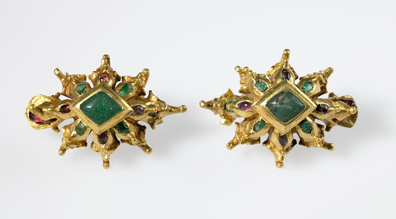 large floral-shaped earrings with green stone set into diamond shape at center; green stone and dark pink glass inlays; 2 prongs on back of each