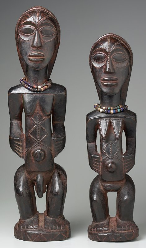 standing female figure with knees slightly bent; triangular breasts; diamond and lines on stomach; long hair; 2 strands of multicolored beads around neck