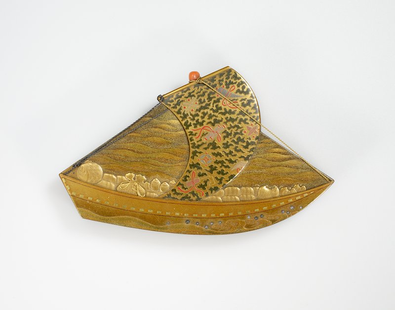 Box, gold lacquer, in shape of sampan, on the sail of which appear symbols in red and black amid black clouds. The sampan is loaded with barrels and bags. A piece of coral represents the top of the mast, and metal threads are used for ropes.