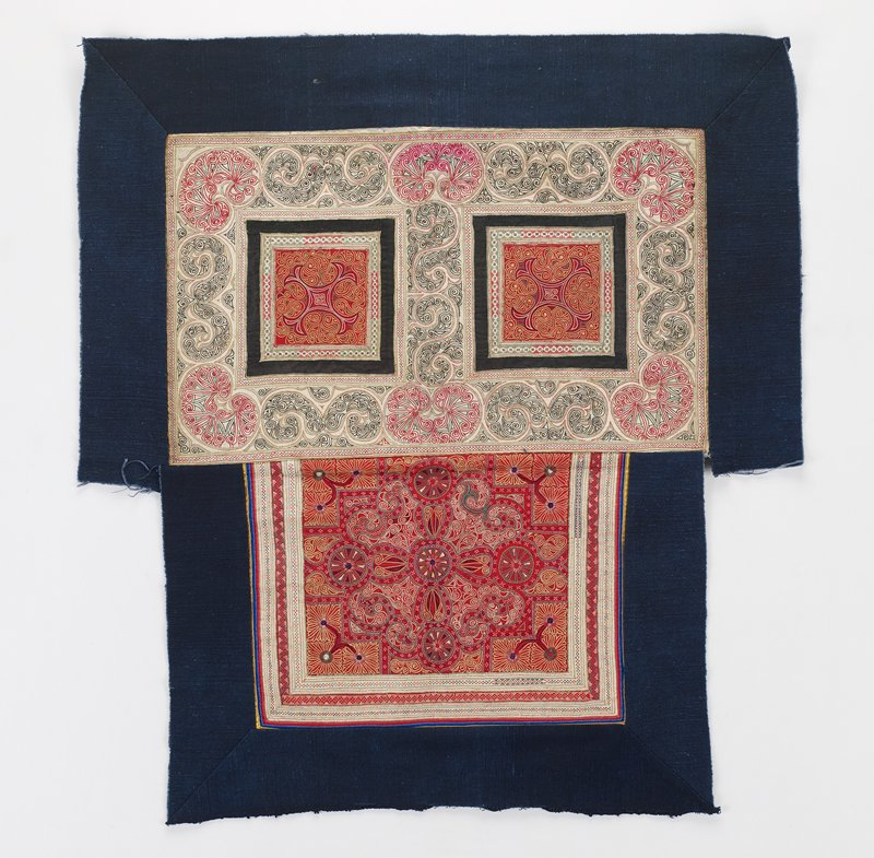 upper section with 2 squares of embroidery on red with black ribbon borders and multicolored scrolls around edges; lower rectangle with circular design and abstracted flowers; blue borders