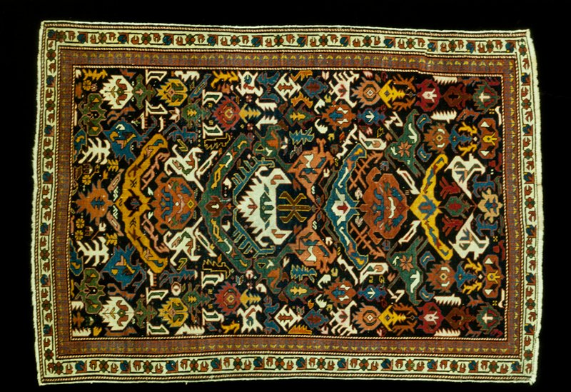 Rug, so-called 'dragon' type; dark blue field witrh geometrical floral and leaf designs, hook and 'S' shapes in blue, green, red and white. Two borders seperatews by a barber pole guard stripe. The outer stripe has a geometrical flower and knop pattern connectedd by vines on an ivory field. The innner border is of wine glass design on a rose field. Selvedged with cotton, short warp fringe at each end. Closely woven with nap cut very short. Ghiordes knot. Woolen warp; cotton woof.