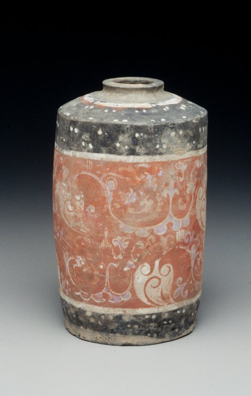 cylindrical jar tapered sharply at top terminating in a rimmed 1-1/8 in. opening; exterior decorated by a large organic motif; central band of red, blue and white; two smaller bands of white and black with pairs of white dots encircle the base and top