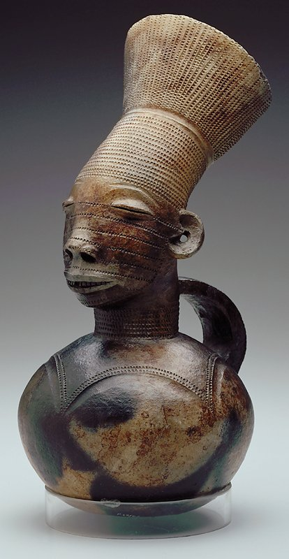 vessel with handle, surmounted by female head; opening of vessel is through top of figure's headdress; surface has glossy appearance; dark clay body