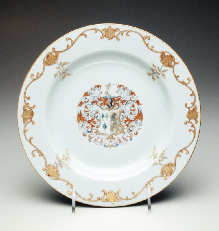 plate decorated with famille rose armorial, central coat of arms of Foulis impaling Jones, crest within feathery mantling border with black and gilt baroque shellwork meander; one of a pair