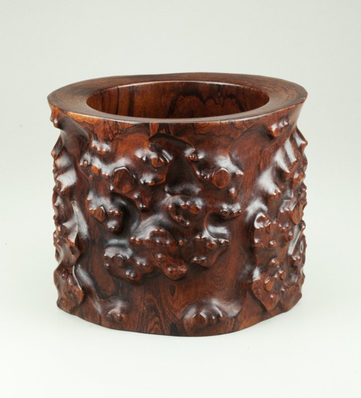 carved exterior imitates root texture; repeated s-curve in carved design; circular raised platform at bottom of bowl, removes from pot
