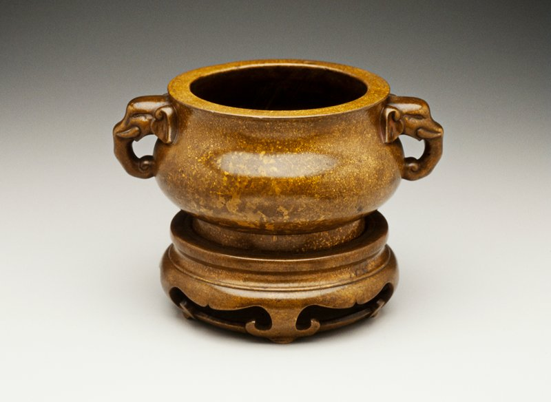 bombé form with elephant head handles; stand with five trefoil-shaped feet joined by a circular stretcher; olive brown surface splashed with gilding