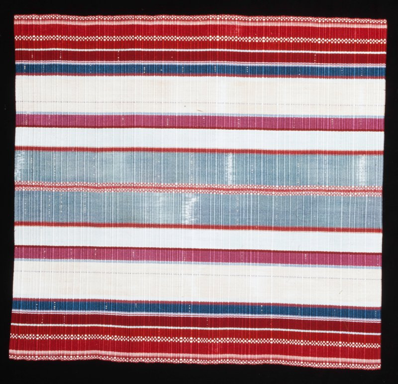stripes of various widths and colors, mainly red, grey and pink; silver colored thread; ends folded over at top and bottom and finished with black cloth; wooded hanging bracket at top