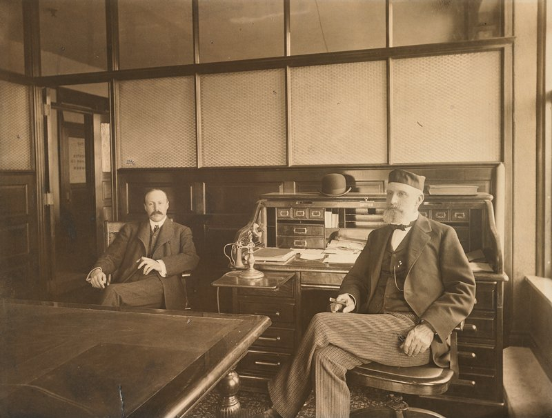 2 men in suits seated in an office; older bearded man at R seated in front of a desk with a telephone; younger man with mustache at L; table in LLC