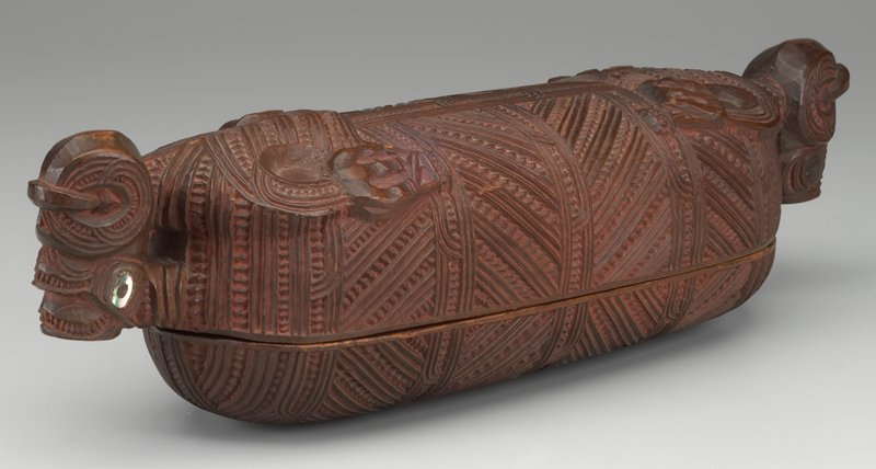 ovoid in shape with tiki head at each end and body carved below; deeply carved geometric design overall