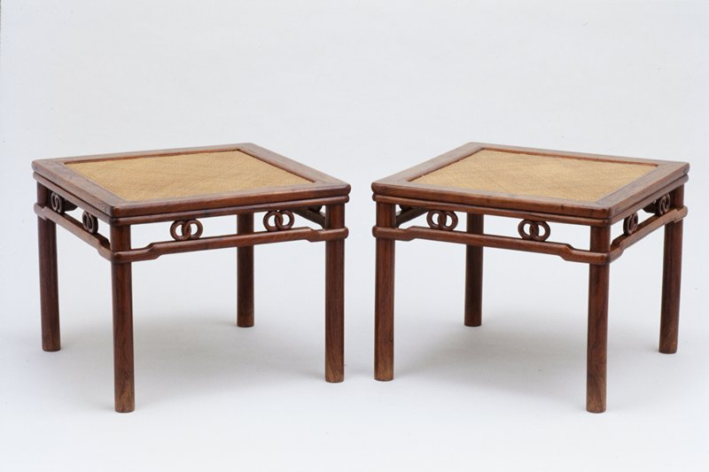square stool with woven seat; round legs and apron elements; apron has two sets of interlocking rings at each side below seat