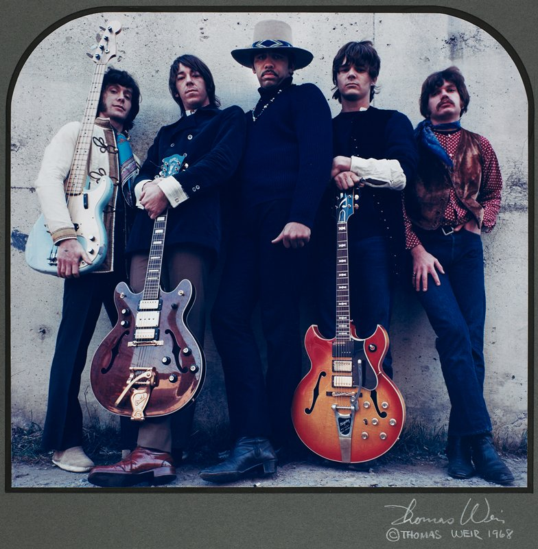 rectangular image, with rounded top corners; 5 men leaning against a wall; center man wears hat, 3 others hold guitars