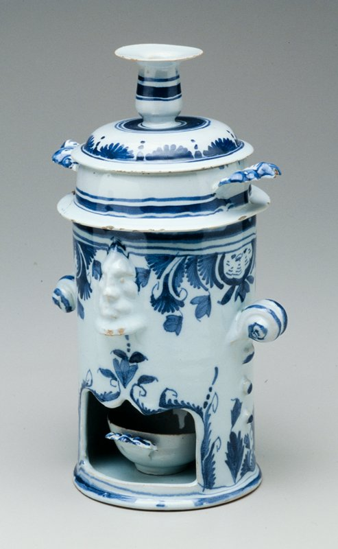 ceramic food warmer, blue and white organic motif; leaves form handles to bowl and oil warmer; two faces protrude from stand covering vent holes; two scroll handles on either side of stand