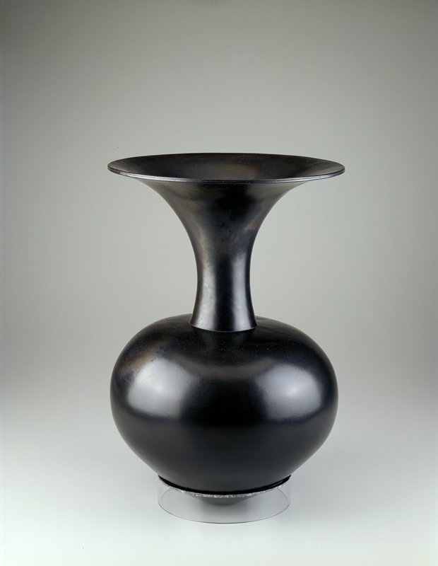 circular body, lower body angled to small circular foot; long neck terminated by a wide flaring mouth; black high gloss glaze; thin wall construction