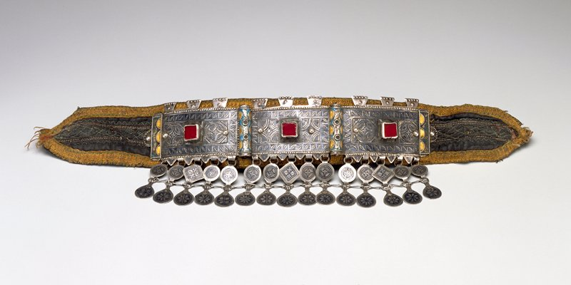 three segment rectangular metal band mounted to a silk headband with ties; etched geometric designs broken by enamel cylinders and square studs; double row of hanging coins at bottom edge