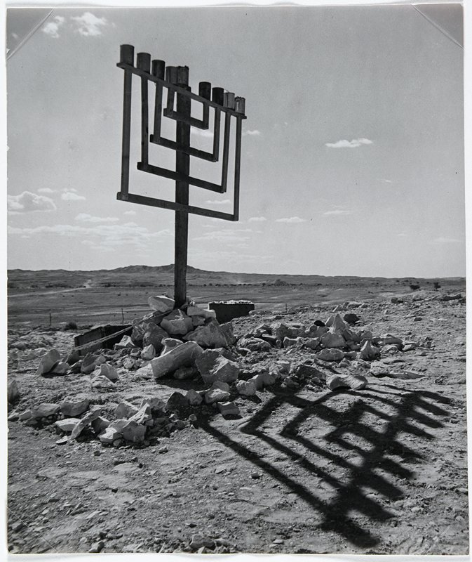 menorah with rocks piled around base outside