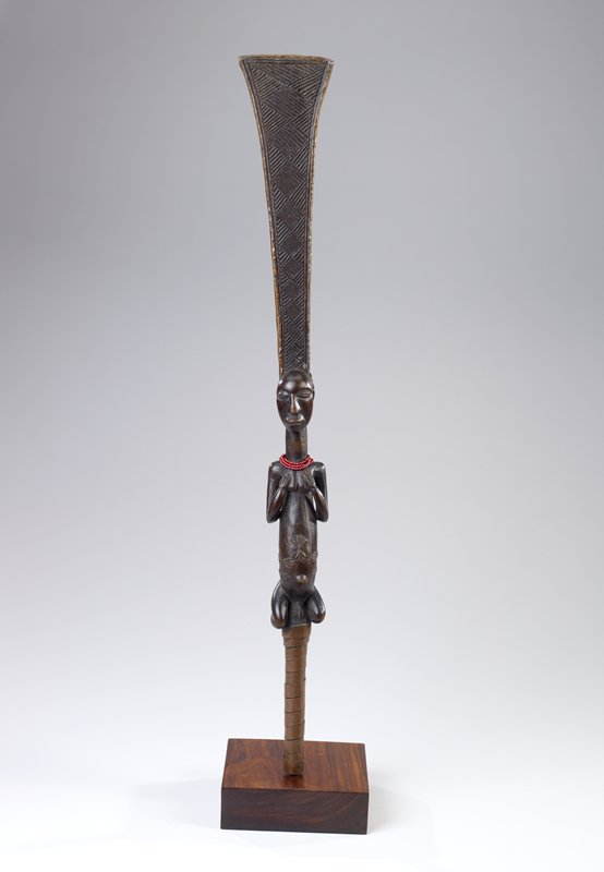 short staff with male figure at center, squatting, with hands on chest; wedge-shaped section extending from man's head creates top of staff; lower portion wrapped with copper strip; figure wears 3 strands of red beads