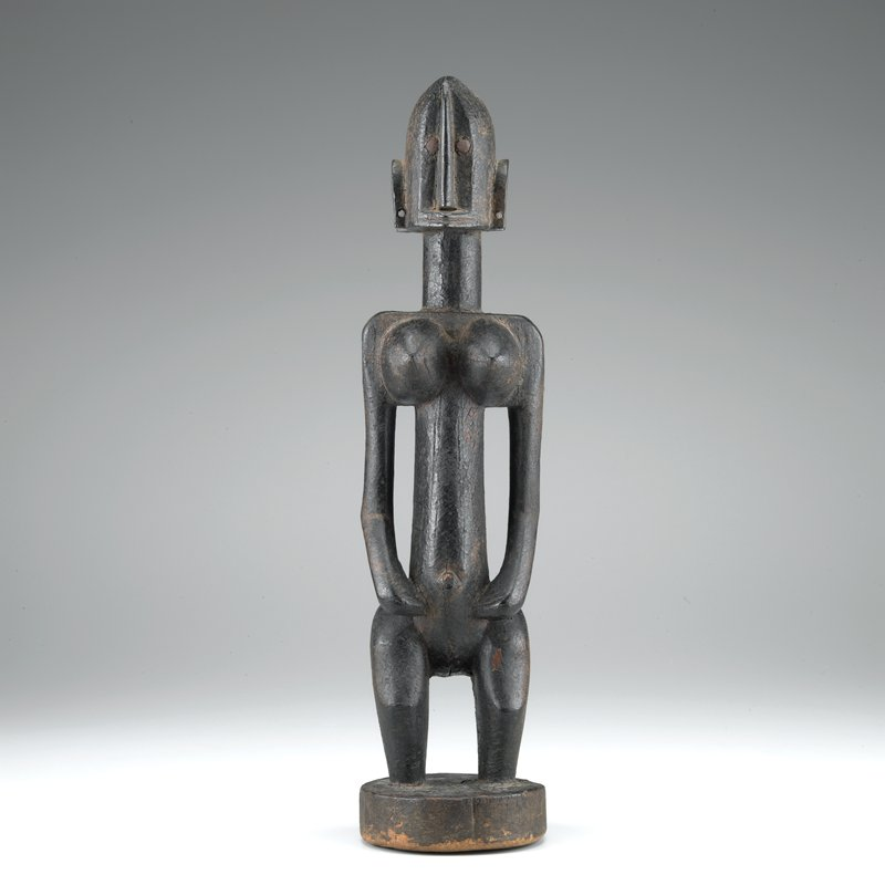 standing stylized figure with geometric features; resinous coating; nailhead eyes; hands on abdomen, knees slightly bent