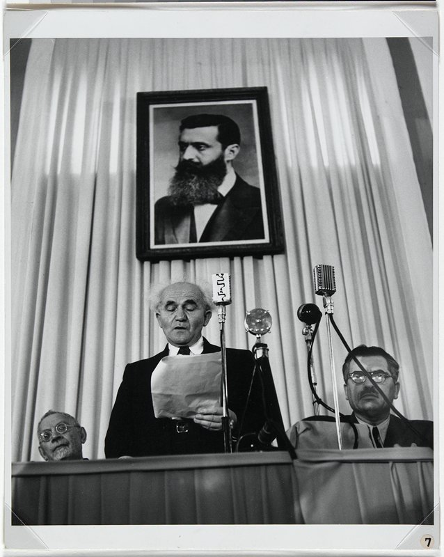 three men at podium with framed portrait behind; center white-haired man reading