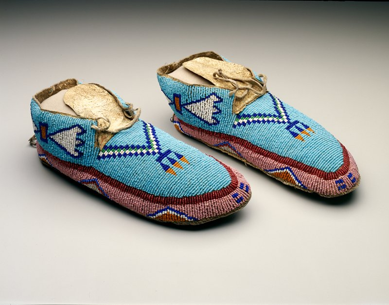 each with parfleche sole; thread sewn in white; bright green, dark blue and pale orange glass beads; blue flat stitched ground with a checkered wedge and three feathers on the front; stylized butterflies or bow shapes around the heel; narrow beaded strips in translucent red below surmounting pink beaded panels containing triangles and short bars