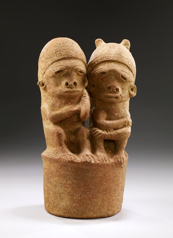 pair of figures seated next to each other; wide bodies and necks; very large lips; figure on R has 2 topknots