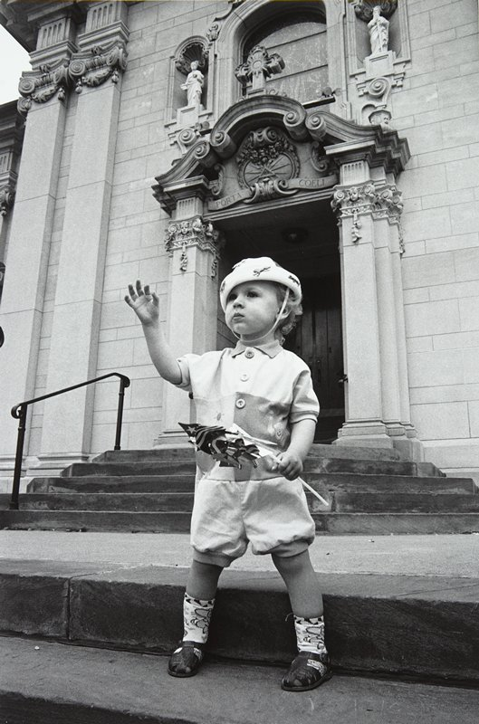 black and white photo of young boy holding pinwheel standing in front of church