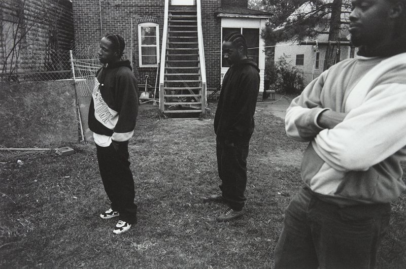 black and white photo of three men standing in yard