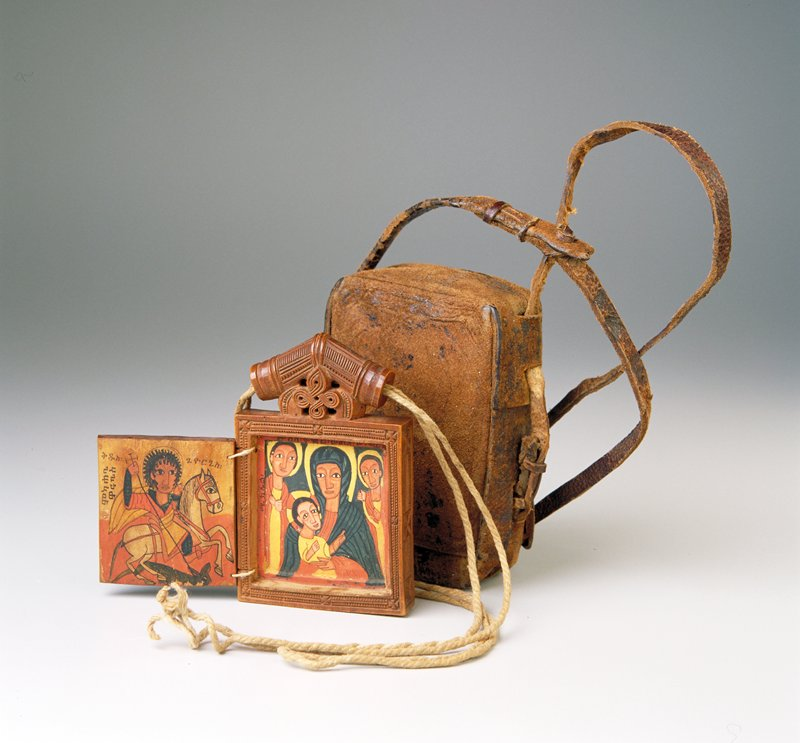 small square carved wood icon with a door on each side attached with string; painted image of madonna and child with 2 angels on inside panel on 1 side and St. George on horseback slaying the dragon on outer door (second door stuck closed); cord threaded through top element of icon attached to cloth bag; 2 part leather pouch with strap for storage