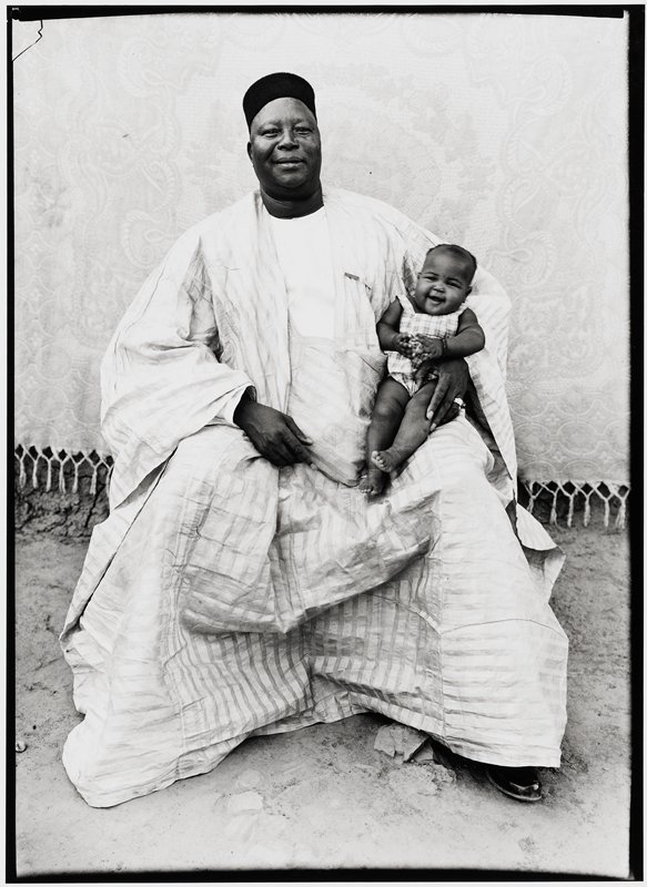 large man seated and dressed in a loose boubou, a white smock (forokoni) and a black fez, holding his daughter on his left leg. Dressed in a loose boubou, a white smock (forokoni), and a black fez, this wonderful giant known to everyone in Bamako is proud of his lovely daughter.