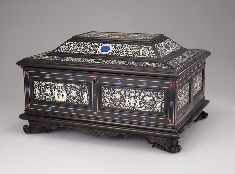 ebony hinge covered box with scroll feet; ivory inlay of geometric floral patterns; side adorned by two panels, floral background with unique pairs mirroring each other banding around each field with inlaid agate cabochons at corners and sides; burlwood interior with seven ivory medallions