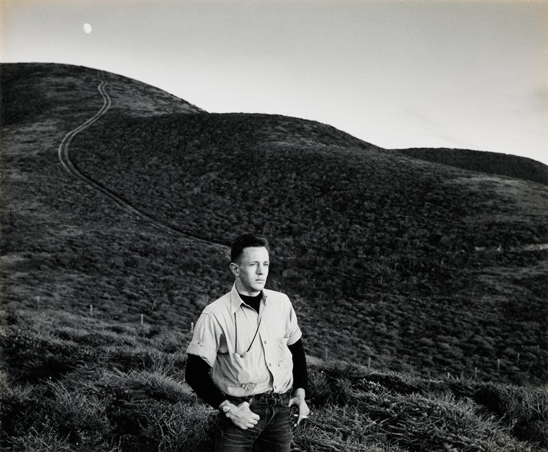 man wearing a light-colored short-sleeved shirt over a dark long-sleeved shirt in foreground; gentle hills with a trail in background; moon at ULC