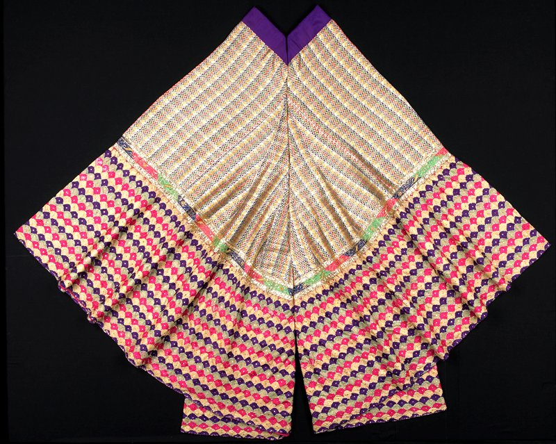 multicolored top portion with triangular woven design; purple waistband; multicolored band with gold thread and sequins in organic design, flanked with gold lame bands; purple, yellow, green and pink scalloped rows at cuffs, appliqued with gold metal bands