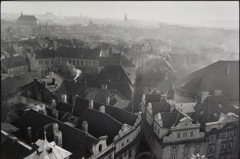 black and white photo of city building roof tops; hazy in the distance