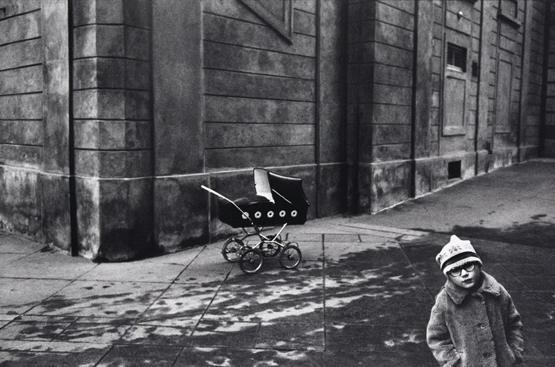 black and white photo of child in hat and coat in LR corner with pram in center of sidewalk