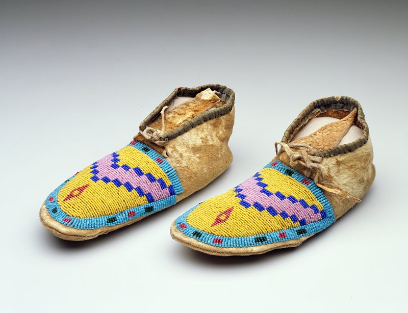 Hide upper and side with hide ties at front; green printed cloth trim around opening; long, pointed tongue; beaded on top of foot overall with geometric designs in blue, green, red, pink and yellow beads