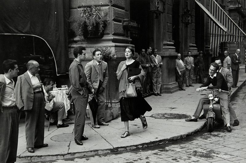 young woman wearing sandals, a shawl and a dark-colored dress, walking down a street where standing men, men seated at a cafe and men on a motorbike gaze at her