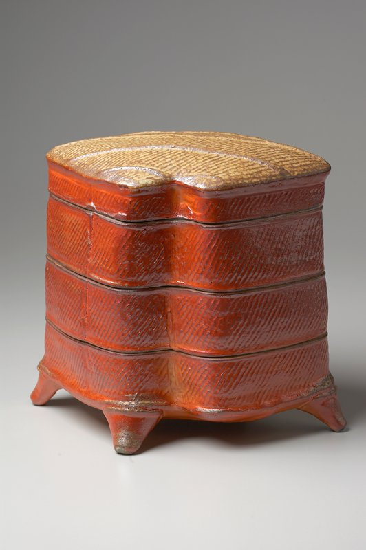 base with slightly protruding feet; 2 trays and lid fit on top of base; rectangular in shape with 2 opposite corners indented; orange on sides with diagonal hatching; top is mustard yellow and brown with ribbed design, grey interior