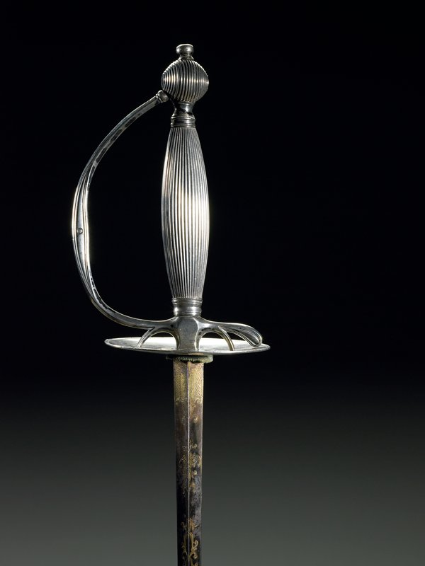 antique silver sword; linear decoration on handle; iridescent blue/purple stain at base of shaft with carved decoration. Arms and Armor-Edged Weapon