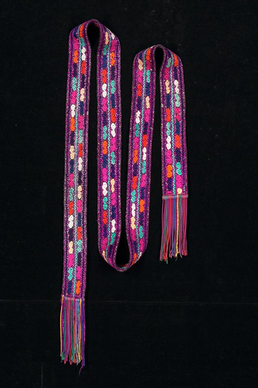 long band with orange, green, black, pink, white flowers against magenta ground; ends in colored fringe